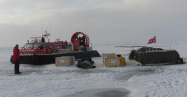 Den norske isdriftsstasjonen FRAM-2014/15 med utstyr og forsyninger med deltaker Audun Tholfsen, Longyearbyen i forgrunnen. Foto: Nansensenteret, Yngve Kristoffersen.