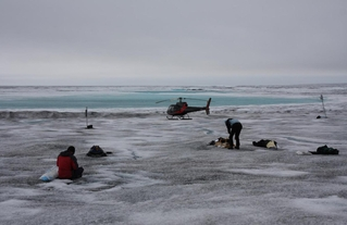 At work on heavily discolored ice in the 'dark zone' on the Greenland Ice Sheet in 2010. Courtesy: Black and Bloom Team.