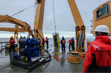 CANAPE Mooring recovery. A 2000 lbs Teledyne Webb Research swept-frequency source being lowered onto the deck. A hydrophone module can be seen clamped to the wire, right above the source.