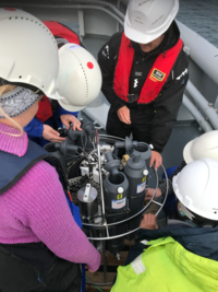Students investigating the water sampling bottles on the frame holding bottles and CTD sensors.: Photo: Hanne Sagen, NERSC